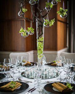 Rendhagyó magas asztaldísz mogyoróágon fiolákkal