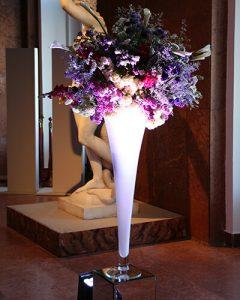 Rendezvénydíszítés nagy fehér vázában lila virágok