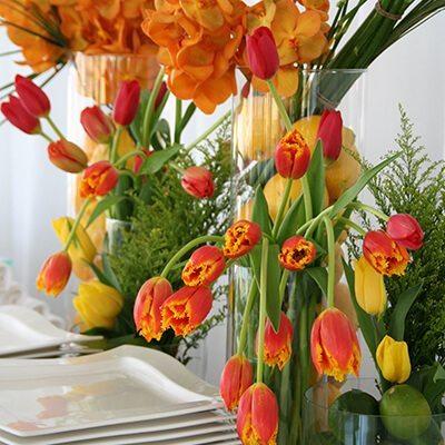 Egzotikus büfédekoráció gyümölcsökkel és sárga-piros virágokkal