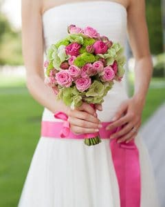 Green and pink bridal bouquet in hands of bride with pink belt