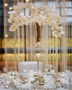 Wedding table decoration of orchids in silver chalice