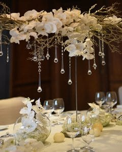Wedding table decoration out of snow white orchids with crystals.