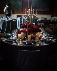 Férfiasan extravagáns dekoráció vörös rózsákból arany gyertyatartóval