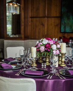 Elegáns lila asztaldísz bazsarózsából, gyertyákkal