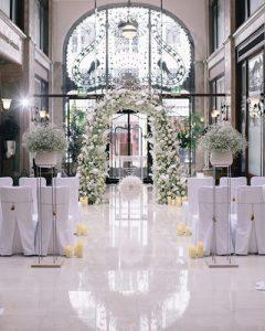 Pazar fehér esküvői fogadás díszítése virágkapuval, virágállványokkal