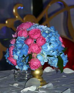 Kék hortenzia lila peóniákkal arany talpon, koktélasztalon