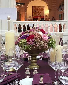 Elegáns asztaldísz vegyes virágokból arany talpon