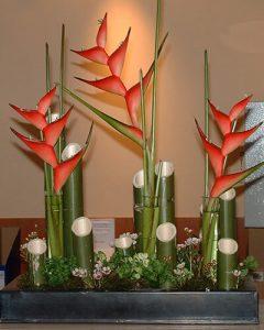 Piros helikónia virágok bambusszal tárgyaló asztalon