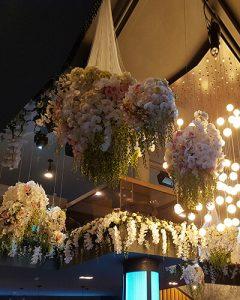 Pazar fehér virágcsillárok térben lógatva
